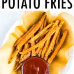 Oval bowl lined with parchment paper and filled with crispy baked sweet potato fries. A small bowl of ketchup is in the next to the fries.