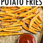 Crispy baked sweet potato fries on parchment paper next to a small bowl of ketchup.