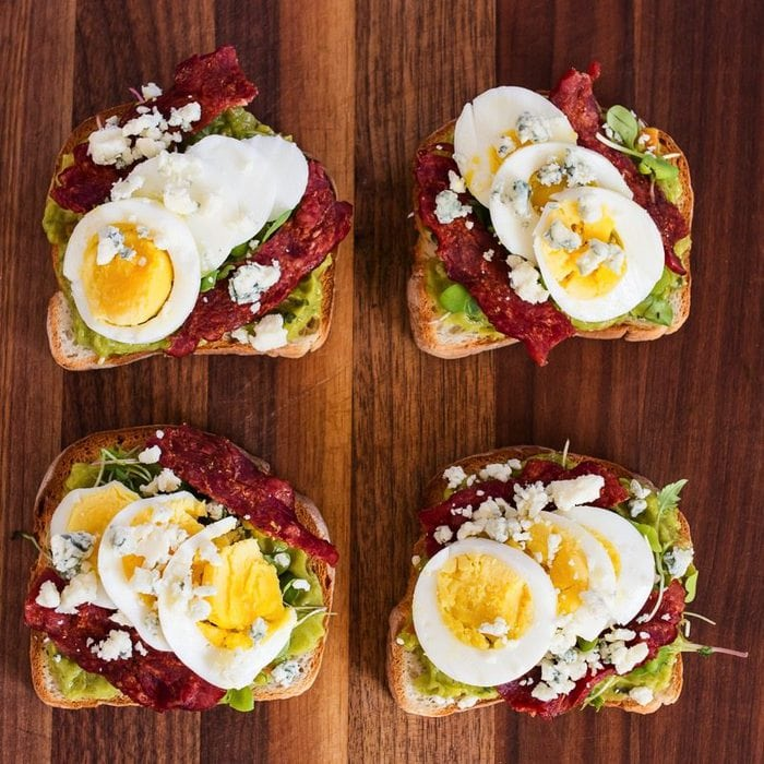 Turn toast into lunch with this veggie-packed cobb salad avocado toast — loaded with hard boiled egg, turkey bacon, blue cheese and micro greens.