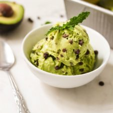 White bowl with mint chocolate chip icecream with fresh mint leaves on top. A spoon, half an avocado and tray are next to the bowl.