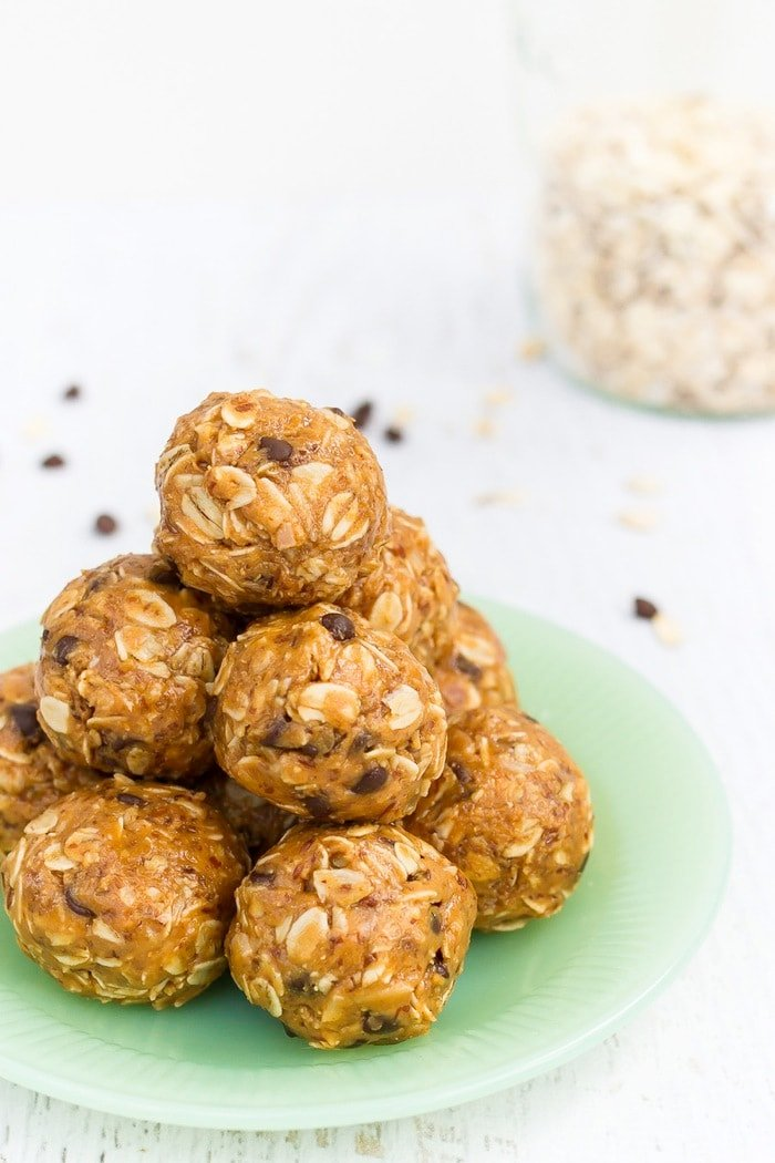 No bake energy balls stacked on a green plate.