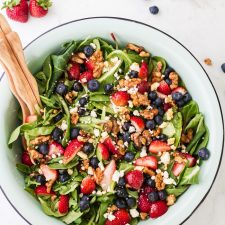 Strawberries, blueberries, nuts, and feta on a bed of greens in a white bowl, a wooden spoon is also in the bowl. Additional ingredients are around the bowl and two glass jars are behind it.