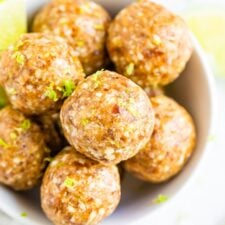 Key lime energy balls in a bowl garnished with lime zest.