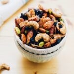 Two bowls stacked, full of trail mix with mixed nuts and dried blueberries.
