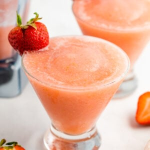 Two glasses with strawberry frosé. Each one has a strawberry on the rim.