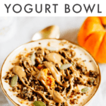 Bowl filled with yogurt and pumpkin and topped with seeds, granola and almond butter. Spoon and pumpkin off to the side.