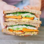 Two hands holding a Autumn Turkey Sandwich filled with apple slices, roasted sweet potato, red onion, avocado and a honey mustard hummus spread, cut in half with the inside of each half exposed.