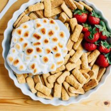 White pie dish filled with strawberries, graham crackers, and a bowl of s'mores dip covered in torched marshmallows. A spoon is next to the dish.