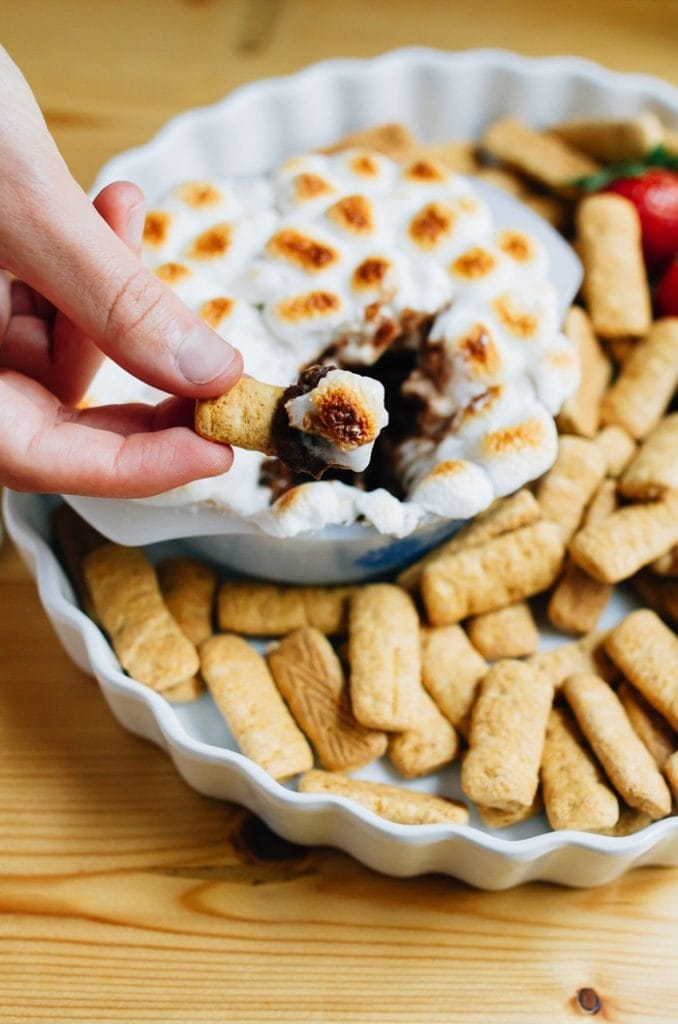S'mores dip topped with toasted marshmallows. Dipped with gluten free graham cracker sticks.