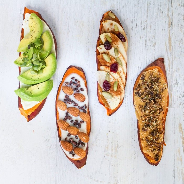 Overhead shot of four Sweet Potato Toasts on a white washed wood table.