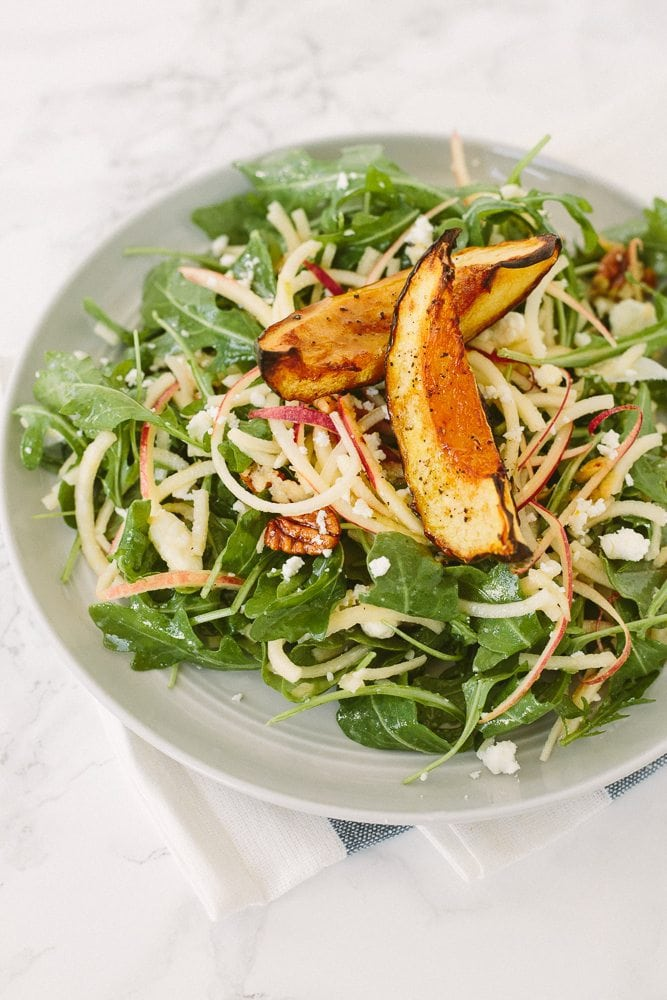 Arugula salad on a plate with spiralized apple and roasted squash and pecans.