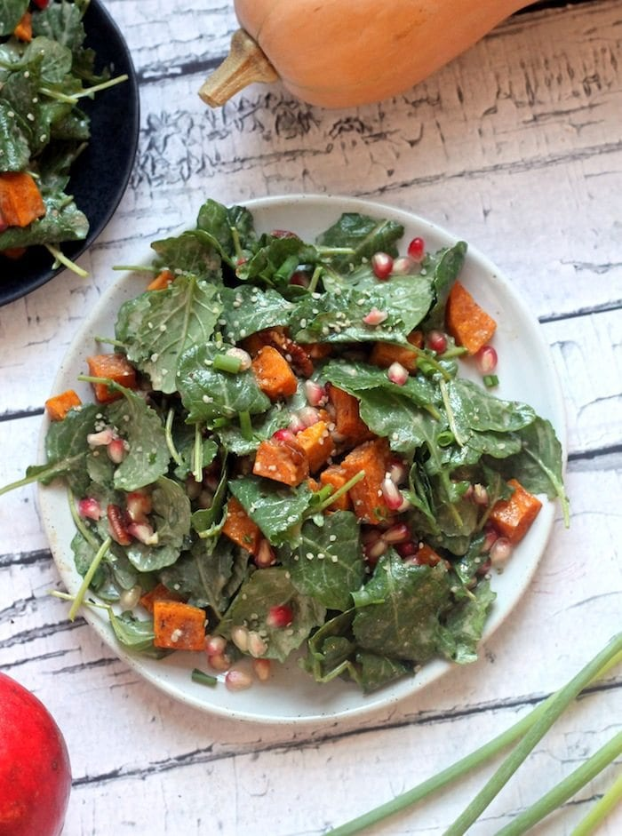 Salad topped with butternut squash, pomegranate and dressing on a plate with squash in the background.