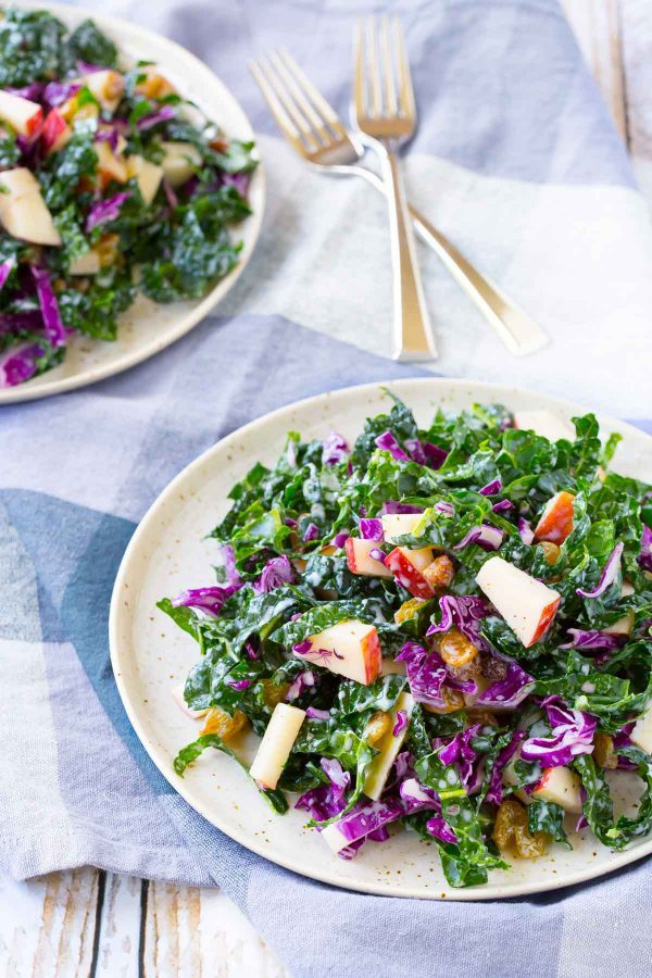 Two plates with kale and apple salad tossed with golden raisins.