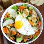 Fall breakfast salad in a bowl with apples, avocado, squash, onion, and walnuts on greens.