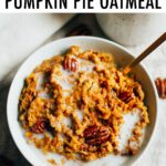 Bowl of pumpkin oatmeal topped with pecans and almond milk.