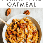 Bowl of pumpkin pie oatmeal with almond milk and pecans on top. Spoon in bowl and pecans scattered around the bowl.