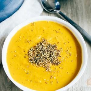 Curried sweet potato soup, spoon, and bowl of hemp seeds.