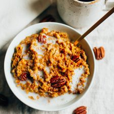 Overhead shot of Slow Cooker Pumpkin Pie Oatmeal in a white bowl with milk and pecans in the bowl.