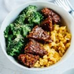 Bowl of yellow rice with tempeh and broccoli.