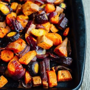 Roasted root veggies on a baking stone, including chopped carrots, sweet potatoes, onions and parsnips.