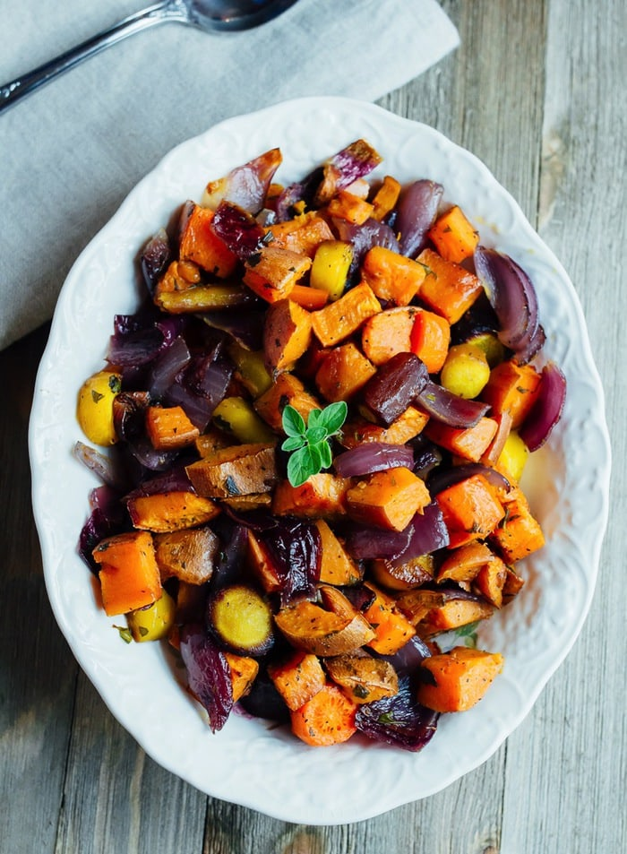Caramelized, roasted root veggies like carrots, sweet potatoes, parsnips, and onions in a serving bowl on a wood table.
