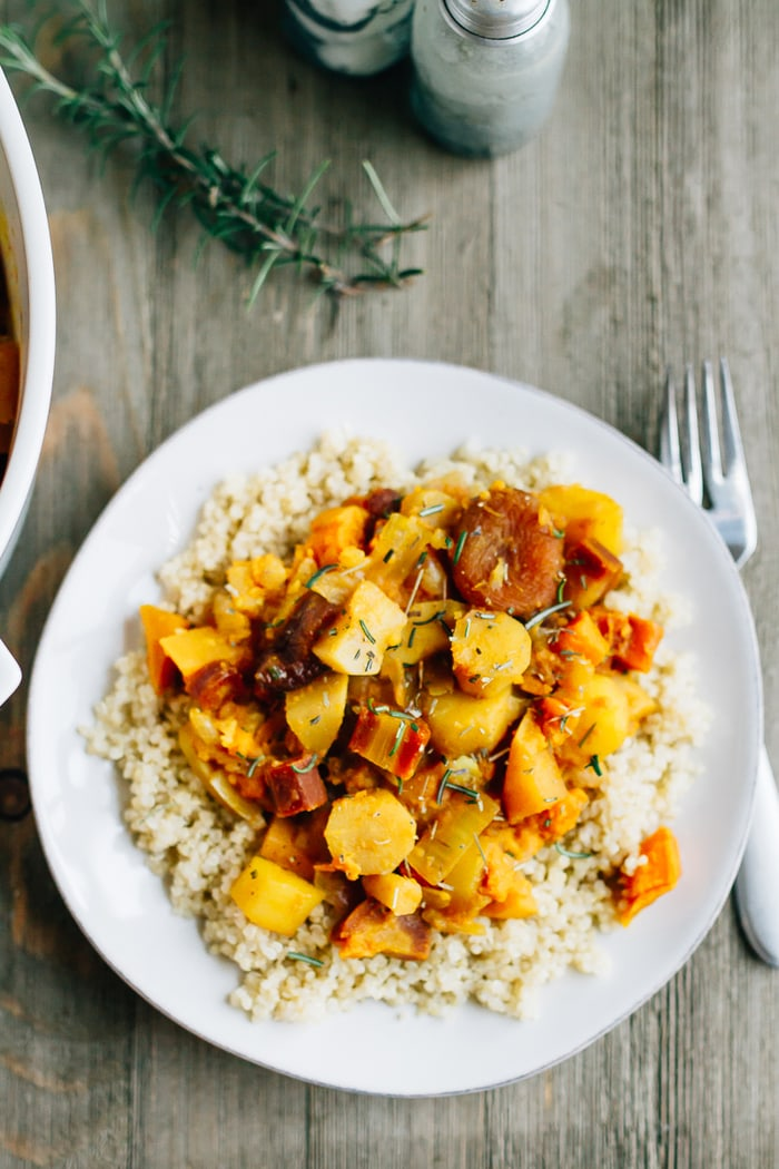 Root vegetable tagine with rosemary and apricots served over a plate of brown rice.