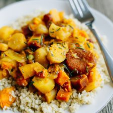 Root vegetable tagine over quinoa on a white plate with a fork.