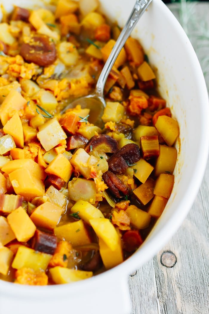 Roasted root vegetables in a dish with dried apricots and topped with rosemary.
