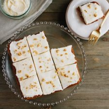 Top down view of carrot cake bars on a cake stand, and a plate with one bar and a fork. Remaining icing in glass cup beside it.
