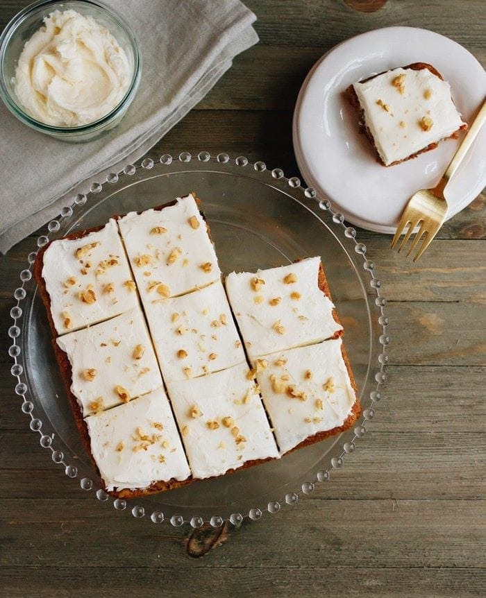 slices of carrot cake bars on a cake stand and on a plate