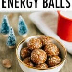 Bowl of gingerbread energy balls on a table with mini Christmas trees and a red enamel mug of milk.