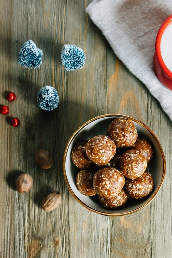 Bowl of gingerbread Larabar balls in a bowl on a wood table, next to mini Christmas trees, jingle bells, nutmeg cloves and a mug of milk.
