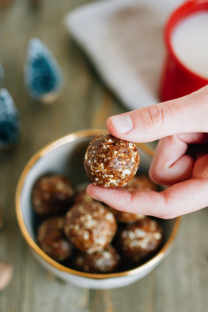 Hand holding a gingerbread Larabar ball over top of a bowl full of balls.