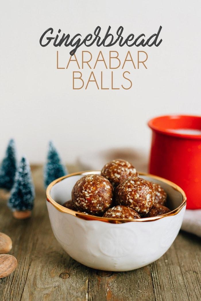 Bowl of gingerbread Larabar balls next to Christmas dress decorations and a mug of milk.