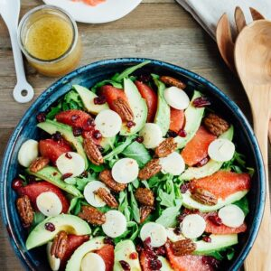 A festive winter grapefruit avocado salad with peppery arugula, hearts of palm, candied pecans, dried cranberries and a maple apple cider vinegar dressing. A plate of grapefruit, serving spoons, and cup of dressing are on the side.