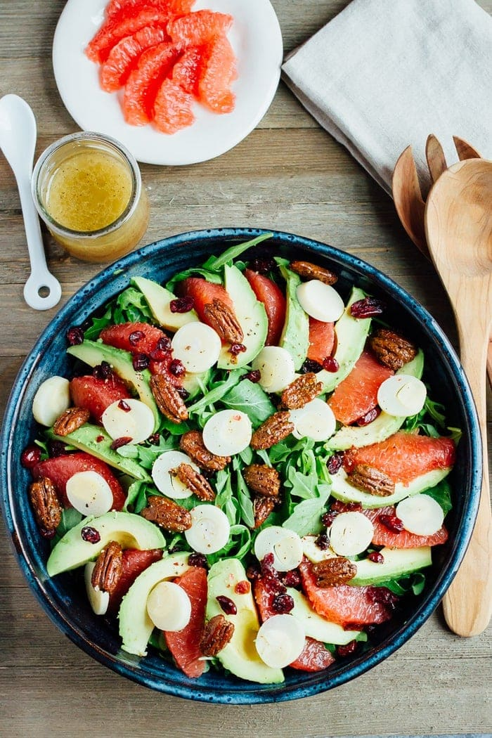 A festive winter grapefruit avocado salad with peppery arugula, hearts of palm, candied pecans, dried cranberries and a maple apple cider vinegar dressing.