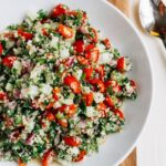 Shallow bowl filled with hemp heart tabbouleh made with hemp, cucumbers, herbs and tomatoes.