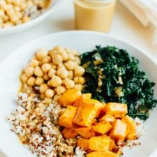 White shallow bowl of brown rice, roasted sweet potato, chickpeas and kale. Drizzled with peanut sauce. The jar of sauce is off to the right-hand side.