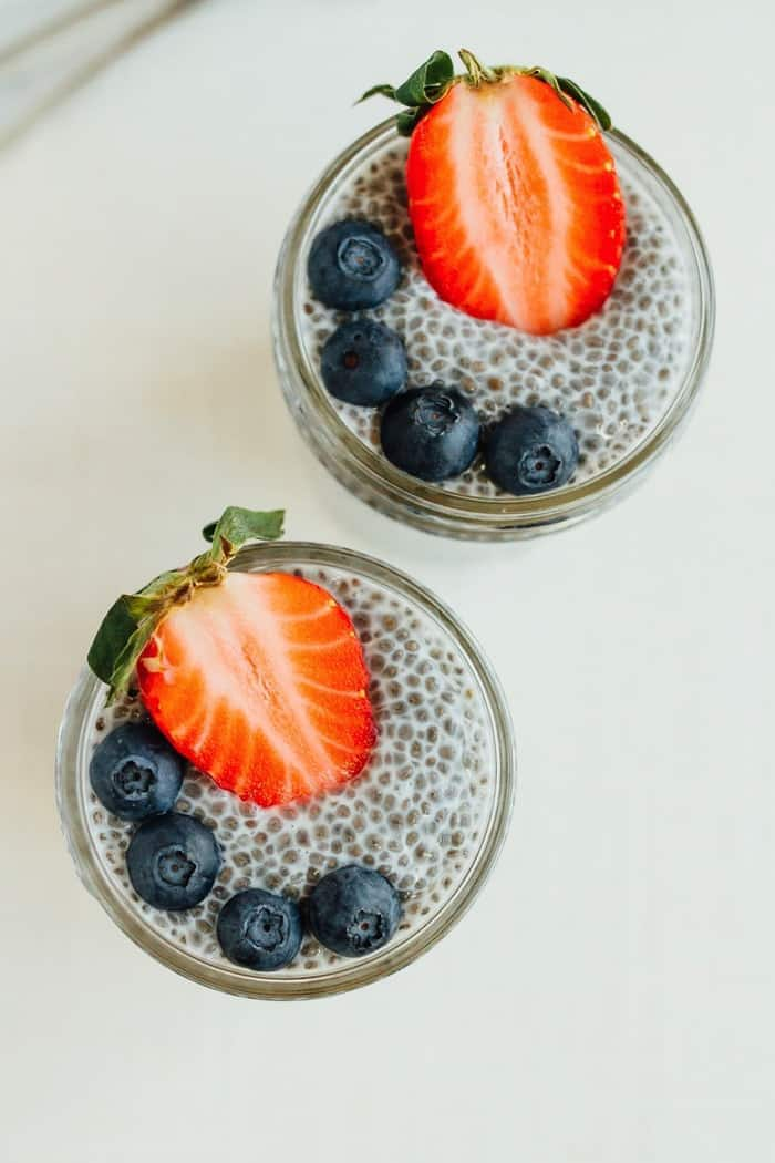 Chia pudding in small mason jars with berries on top.