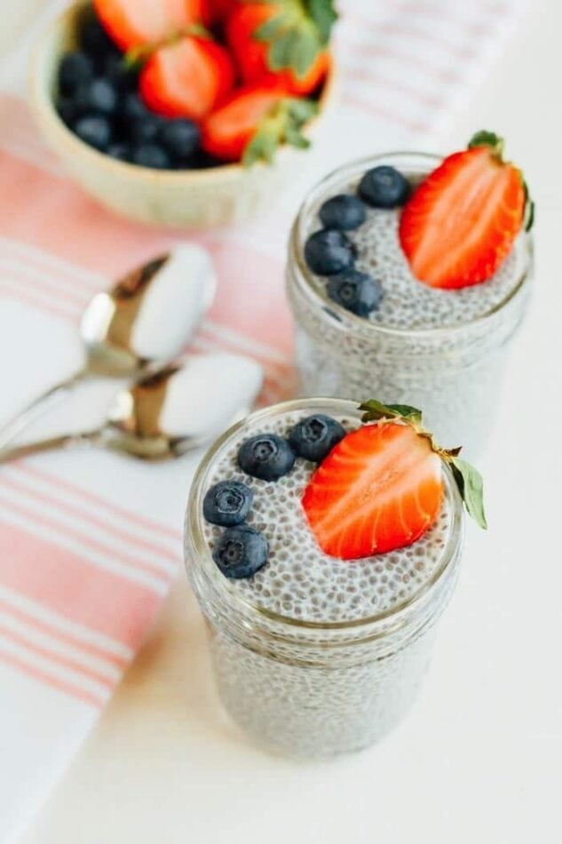 Chia pudding in mason jars with blueberries and strawberries on top.