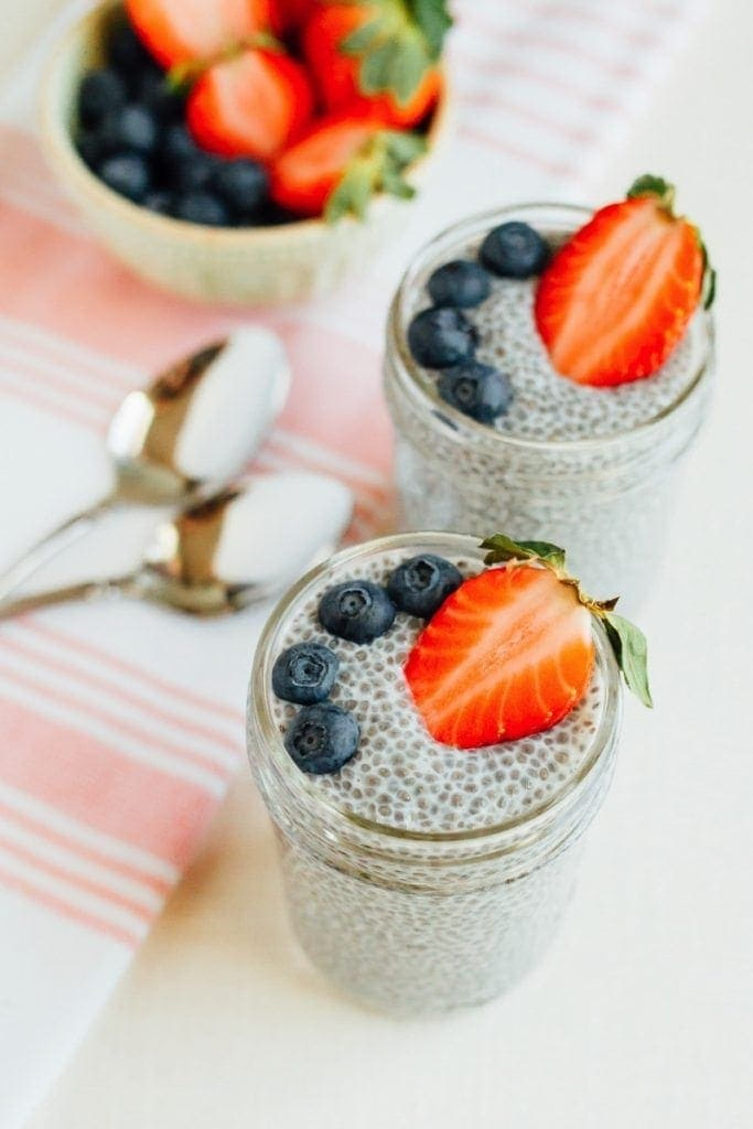 Glass jars with chia pudding, topped with blueberries and strawberries. Napkin, bowl of berries and spoons are to the side.