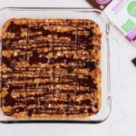 Tray of oatmeal raisin protein bars with dark chocolate drizzle in a baking dish, next to a bar of dark chocolate.