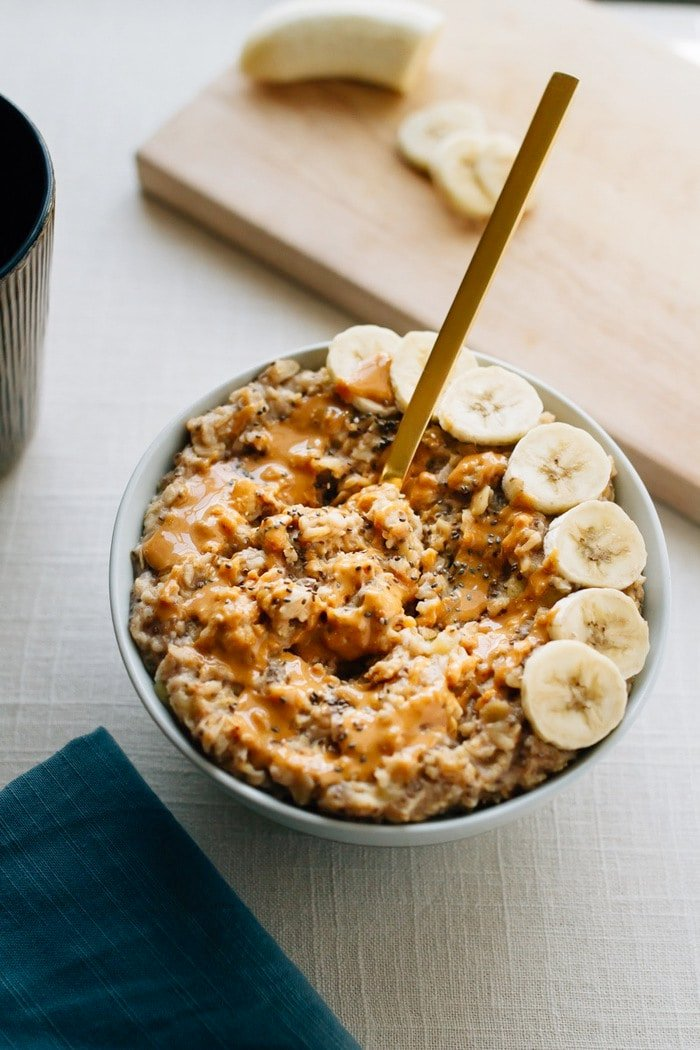 Bowl of oatmeal with chopped bananas arranged on one side of a bowl, peanut butter drizzled on top and a gold spoon sticking out of the bowl.
