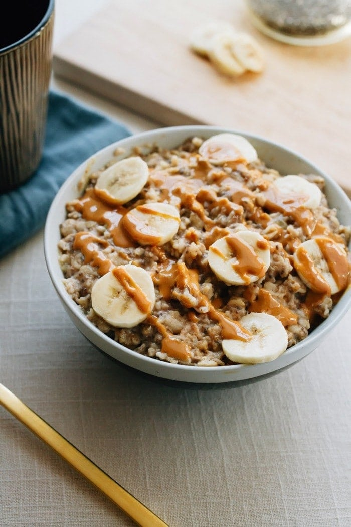 Bowl of oatmeal with chopped bananas and drizzled peanut butter on top.