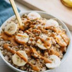 Bowl of oatmeal with chopped bananas and drizzled peanut butter on top. Gold spoon sticking out of the oatmeal. Cutting board with chopped banana out of focus in the background.