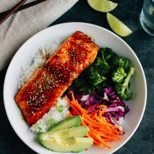 Teriyaki salmon over white right with avocado, carrots, purple cabbage, and broccoli, with chop sticks, slices of lime, and a napkin next to it.