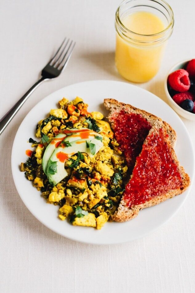 Turmeric tofu scramble on a plate with avocado on top. Two slices of bread with jam on the side. A bowl of raspberries and blueberries is next to the plate. Glass of orange juice and fork also on the side.