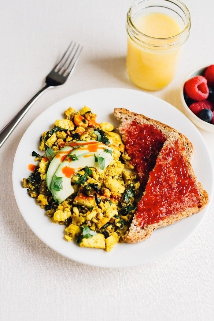 Turmeric tofu scramble on a plate with avocado on top. Two slices of bread with jam on the side.