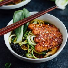 Two bowls of ramen made with tempeh, zucchini noodles, dried seaweed, and bok choy, with chopsticks on the bowl ledge.