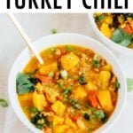 White bowl and spoon with turkey chili made with lentils, butternut squash and kale.
